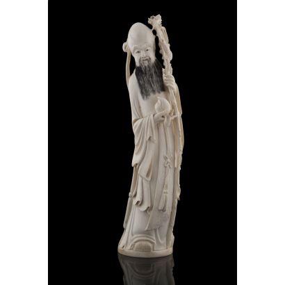 Escultura en marfil con detalles policromados, representa a deidad masculina con báculo y fruto. Marca en base. Con certificado de antigüedad. Alto: 32cm.