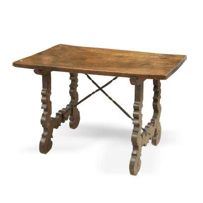 Mesa castellana, S. XVII.  Realizada en madera de nogal con fiadores de hierro. Presenta pata de lira recortada.  Medidas: 77 x 115 x 68 cm.