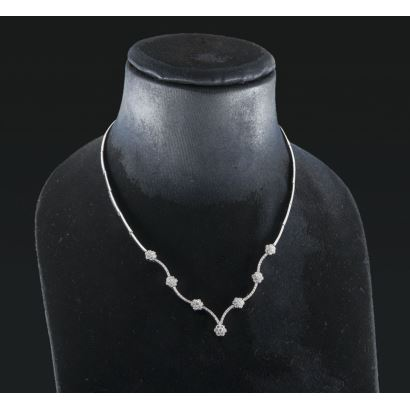 Exquisito collar de oro blanco 18K decorado en la zona del escote con 7 rosetones articulados entre barritas curvadas, todo ello con 1,80 quilates de diamantes talla brillante. Peso 24,70 gr.
