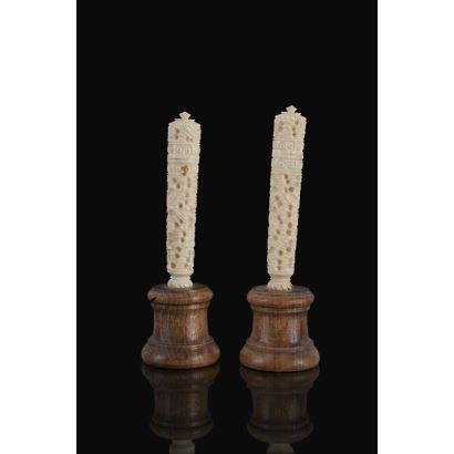 Pareja de tallas tubulares con tapa realizadas en marfil sobre peana de madera. Alto: 7,5cm c/p 11cm.