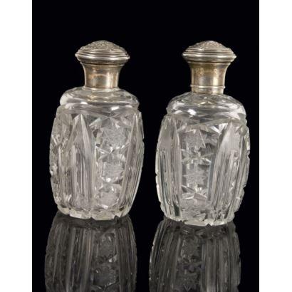 Elegante pareja de frascos de cristal tallado, ambos cuentan con tapa en plata con finos motivos florales en relieve. 22x11cm.