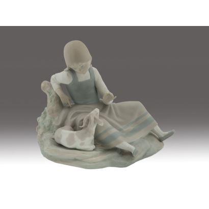 Porcelana. Figura en porcelana de LLadró, siglo XX. Niña sentada con carnero policromada. Sellada en la base. Medidas: 23 x 28 cm.