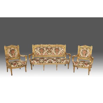 Conjunto de sofá y sillones, en madera tallada y dorada con ricos motivos florales, cuentan con tapicería floral sobre fondo blanco. Estilo Luis XVI,  s.XX.