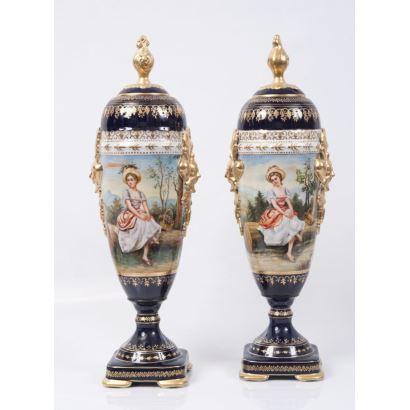 Pareja de jarrones en porcelana policromada y dorada sobre fondo azul cobalto, presentan franja central con escenas campestres de damas. Marca en base. Medidas: 58x20cm.