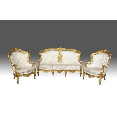 Tresillo compuesto por sofá y dos sillones, con madera tallada y dorada y tapicería floral sobre fondo marfil, rica decoración floral en brazos y patas. Siglo XX. Medidas sofá: 119x187x68cm; medidas sillones: 118x88x72cm.