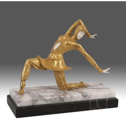 Figura crisoelefantina de inspiración Art Decó, representa a una bailarina sobre una rodilla,  sigue el modelo del célebre escultor Chiparus, la pieza esta realizada en bronce dorado y marfil sobre peana. Con CITES 28x23x1cm c/p 33x13x27cm.