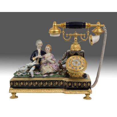 Bonito teléfono realizado en porcelana policromada con fondo azul cobalto y apliques dorados al oro fino, la base alberga en bulto redondo  a una pareja dieciochesca. Medidas: 34x37x20cm.