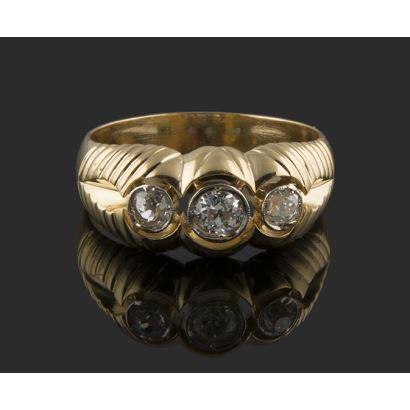 Tresillo en oro amarillo de 18K, con tres diamantes talla brillante antigua, con detalle a modo de hilo trenzado en oro blanco de 18K. Total diamantes: 0,38 quilates. Peso: 7,82 gr.