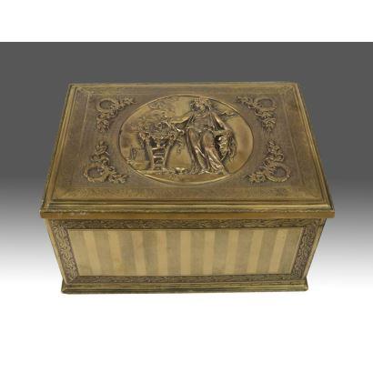 Bonita caja dorada de estilo Neoclásico con relieve en tapa abatible donde observamos una vestal clásica haciendo ofrendas. 14x18x25cm