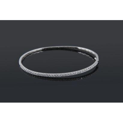 Joyas Selectas. Excepcional pulsera rígida de oro blanco, la mita cubierta por hilera de brillantes H-SI que suman 1cts.