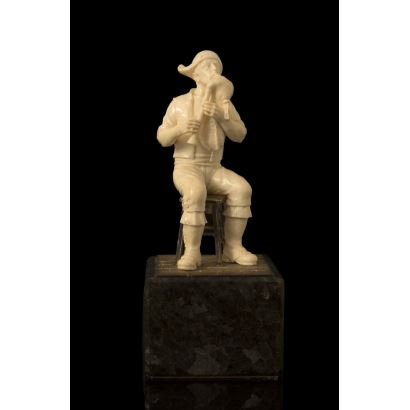 Figura costumbrista realizada en marfil sobre peana, representa a un gaiteiro con gaita sentado sobre taburete.  Alto: 13,5cm, con peana: 20cm.