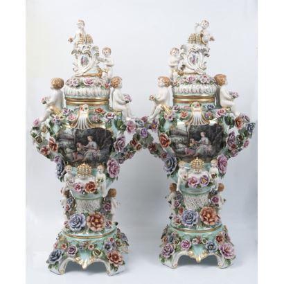 Pareja de jarrones con tapa en porcelana policromada y rica decoración floral en relieve, albergan escenas galantes en medallones sobre fondo verde. Marca en base. Medidas: 95x35x35cm.