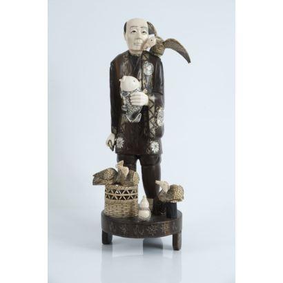 Criselefantina en madera y marfil, pps. XX. Figura de tema costumbrista de pescador chino con cesta. Madera y marfil policromados. Sobre peana circular de madera. Altura: 40 cm.