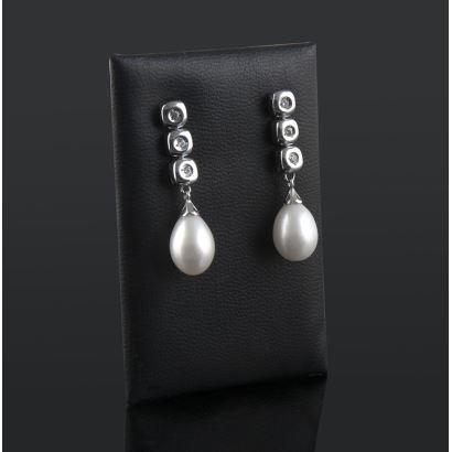 Pendientes de oro blanco con tres chatones con brillantes que suman 0,18cts y de los que pende una perla perilla.