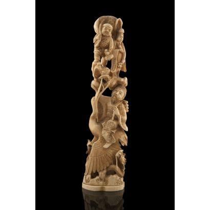 Grupo ricamente tallado en marfil, representa a un personaje masculino sobre una garza, sobre éste una pareja de hombre y mujer con diversos objetos. Firma en base. Con certificado de antigüedad. Alto: 33,5cm.