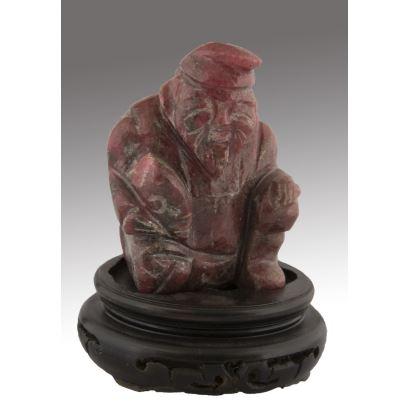 Figura tallada en piedra roja sobre peana de madera, representa a uno de los dioses Inmortales Hsien. Medidas: 7x5cm c/p 9x6cm.