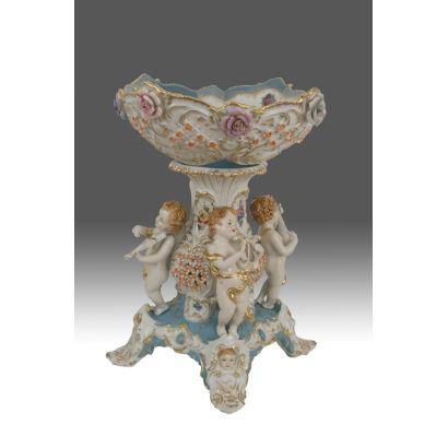 Bonito centro de mesa en porcelana policromada con ricos motivos decorativos en relieve, el pie esta decorado con cuatro angelitos músicos sobre blanco y azul, sujetan un cuenco con detalles calados y florales. Medidas: 53x39cm.