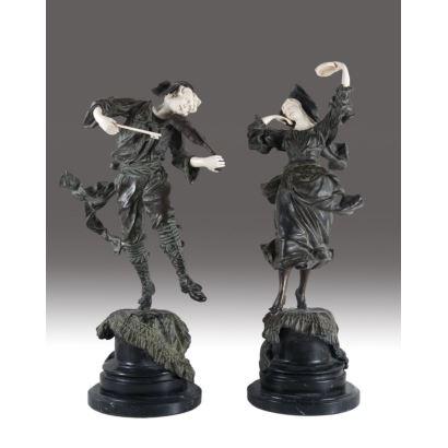 Pareja de criselefantinas, realizadas en bronce con manos y caras de marfil. Representan dos músicos, con violín y pandereta, en actitud de baile. Con peana de mármol. Firmadas en la base. Altura: 66 cm.