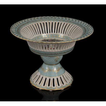 Bello frutero en porcelana, donde observamos calado en la base y el plato superior con decoración floral en el centro con predominio del azul. 22x31x31cm.