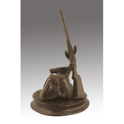 Curiosa figura de bronce, en ella un rifle apoyado sobre un tronco, a su lado una mochila, todo sobre base oval. Altura: 19,5cm. Base: 13,5x12,5cm.