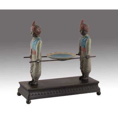 Figura realizada en bronce parcialmente policromada, en ella dos personajes árabes transportan un gran platillo con la ayuda de dos barras, se alza sobre peana rectangular. Medidas: 26,5x11x26cm.