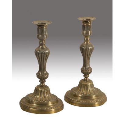 Pareja de elegantes candeleros franceses de bronce dorado, con fina decoración estriada. Medidas: 26x14cm.