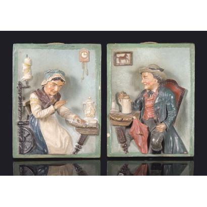 Curiosa pareja de placas de terracota policromadas  en las que vemos en relieve la representación de una mujer hilando y un hombre con una jarra y una pipa, ambos de gusto costumbrista. 23x17cm.