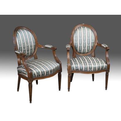 Pareja de sillas estilo Luis XVI, en madera de nogal y tapicería de franjas verdes y marfil, presentan elegantes patas estriadas y respaldo circular. S.XX. Medidas: 94x63x55cm.