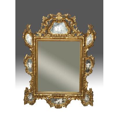 Gran espejo rectangular con marco en madera tallada y dorada con  rocalla, presenta motivos esmerilados de flores y Cupidos en laterales. pp.s.XX. Medidas: 135x107cm.