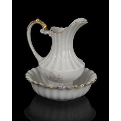 Jarra con aguamanil realizados en porcelana blanca con motivos florales y ribete dorado. Jarra: 13x11cm. Aguamanil: 12cm.