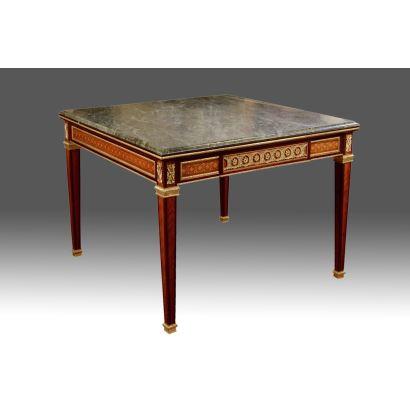 Mesa de juego estilo Luis XVI, en madera con apliques en bronce dorado y tablero cuadrado en mármol verde, presenta patas de estípite y dos cajones en faldón. s.XX. Medidas: 78x100x100cm.