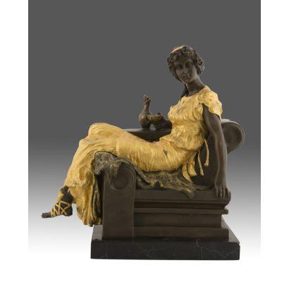 Figura realizada en bronce, cuenta con detalles en dorado, representa a una elegante dama de gusto clásico sentada sobre un asiento. Medidas: 36x33x18,5cm.