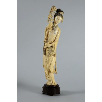 Figura de Guanyin realizada en marfil tallado y grabado. Presenta paipai en una mano y peonías en la otra. Con certificado de antigüedad. Altura sin peana: 30 cm.