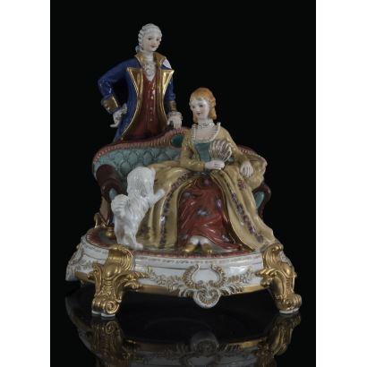 Figura en porcelana policromada y dorada, en ella contemplamos a una dama elegantemente ataviada sentada en un sillón con un perro  mientras que un caballero contempla la escena. Marca en base. 22x25x25cm.