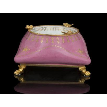 Elegante cenicero con base cuadrada realizado en porcelana en rosa con decoración en dorado  y blanco con motivos florales, cuenta con apliques en bronce dorado al oro fino. Medidas: 11,5x20x20cm.