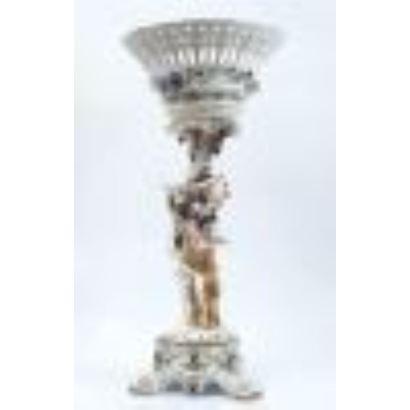Porcelana.  Centro de mesa con estilizado astil decorado con damas entre racimos de vid, cuenco calado superior, fondo blanco. Marca en base. Medidas: 85x38cm.