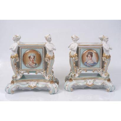Pareja de centros de mesa realizados en porcelana policromada, con figuras antropomorfas en las esquinas, presenta retratos de damas  en medallones sobre fondo azul. Marca en base. Medidas: 34x26x16cm.