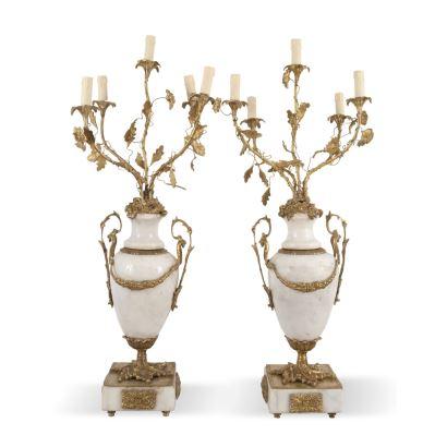 Pareja de candelabros, estilo Luis XVI, S. XX. Realizados en mármol y bronce dorado. Presentan 5 luces. Decoración vegetal y de guirnaldas. Están electrificados. Medidas: 96 x 35 x 32 cm.