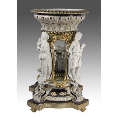 Magnífico centro de mesa realizado en porcelana policromada en el que vemos sosteniendo un cuenco a modo de Cariátides a cuatro figuras clásicas. 72x46cm.