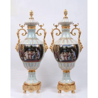 Pareja de jarrones en porcelana policromada, con pie y asas en bronce dorado, cuentan con franja central decorada con escenas galantes sobre fondo azul y blanco. Marca en base. Medidas: 78x14x14cm.