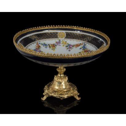 Elegante frutero en porcelana policromada en azul y blanco sobre pie dorado al oro fino, presenta en cuenco rica decoración floral. Medidas: 22x33cm.