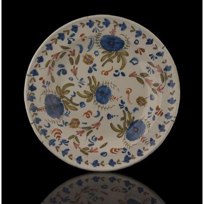 Plato en cerámica de Manises, siglo XIX, con decoración vegetal en azul, verde y rojo sobre fondo blanco. Diámetro: 34,5cm.