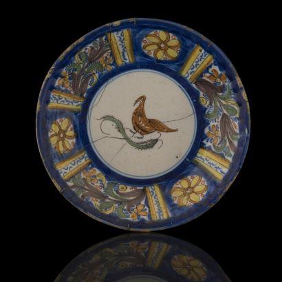 Plato en cerámica de Manises, siglo XIX, con decoración de ave con insecto, presenta rica decoración vegetal en borde. Pieza restaurada. Diámetro: 26cm.