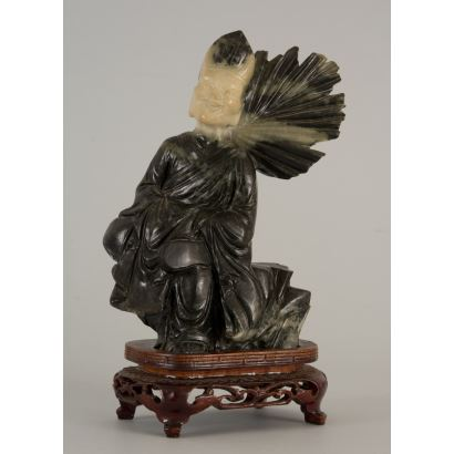 Magnífica figura tallada en piedras duras sobre peana de madera.