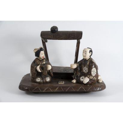 Grupo escultórico oriental realizado en madera y  marfil policromado sobre pedestal, representa a un hombre y una mujer con alimentos bajo palio. Principios del siglo XX. Leves desperfectos.  Medidas: 20x28x17cm.