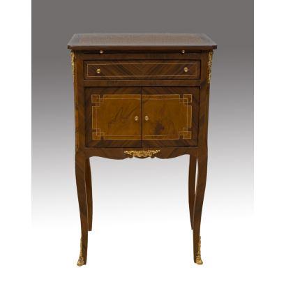 Elegante cómoda con un cajón, doble puerta y tablero extensible oculto entre el cajón y el tablero. La pieza de madera cuenta con apliques metálicos dorados y patas curvas tipo cabriolé. Medidas: 79x48x32cm.