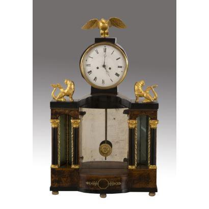 Reloj de sobremesa estilo Imperio, realizado en madera ebonizada y raíz de nogal, con apliques en bronce dorado. Siglo XIX. Maquinaria tipo París. Necesita repaso. No tiene llave ni campana de sonería. Medidas: 61x37x10cm.