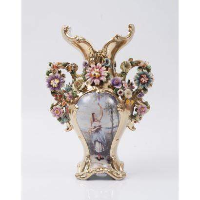 Jarrón realizado en porcelana dorada, con asas florales blanqueando cuello, presenta dos escenas bucólicas en cuerpo inferior.