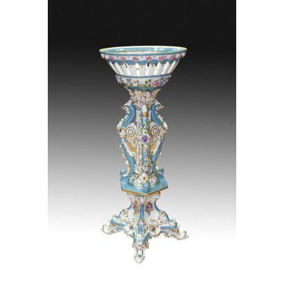 Centro en porcelana policromada en azul y blanco, con estilizado astil de rocallas y cuenco superior calado. Marca en base. Medidas: 104x42cm.