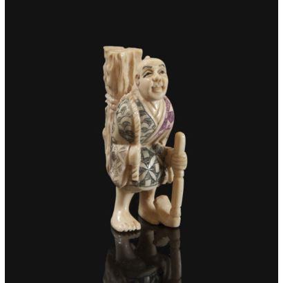 Netsuke, principios S. XX. Leñador. Realizado en marfil tallado, grabado y entintado. Marcas en la base. Medidas: 4 x 4 cm.